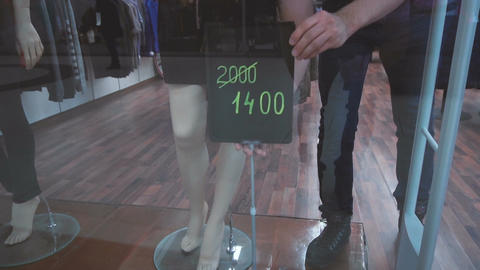 Shop assistant establishes the sign with information about discount Footage