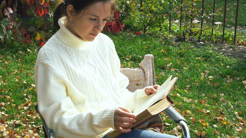 Woman in white sweater reads a book outdoors Footage