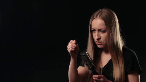 Shocked woman looking at hairbrush. Hair loss Footage