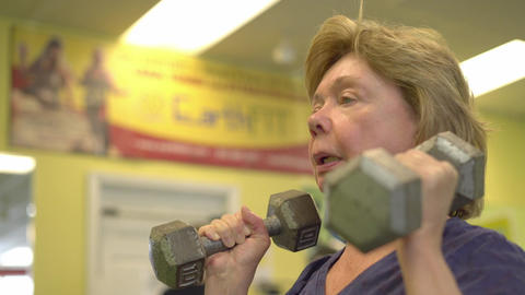 Elderly woman lifts weights over her head Footage