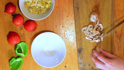 Woman hands slicing mushrooms on rustic cutting board top down view Footage