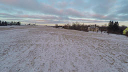 Winter landscape covered in snow at sunset. Aerial footage. Fast low flight Footage