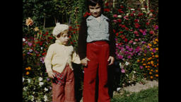 USA 1940s - 1950s: Kids With Sweaters Stroll Through Flower Garden Footage