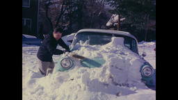 USA 1960s: Digging Out From the Snow, Man Clears Snow From His Car Filmmaterial