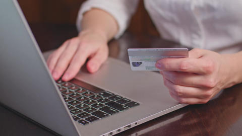 Hands holding plastic credit card and using laptop Footage
