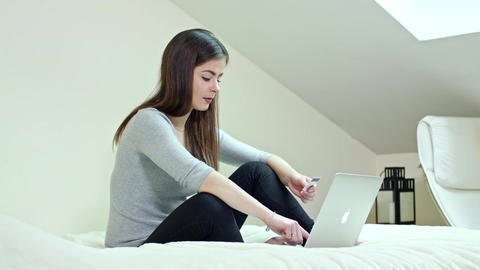 Woman Using a Laptop Sitting on a Bed at Home Footage