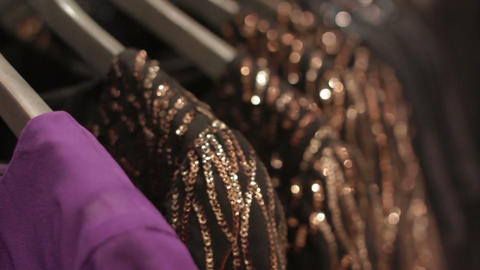 Camera Moves along Clothes Hangers with Elegant Dresses Footage