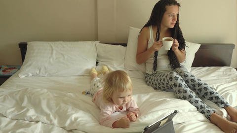 Woman and baby girl watching cartoons on tablet computer Footage