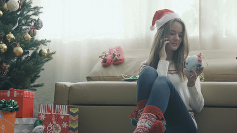 Pretty girl in christmas cap talking on the phone Footage