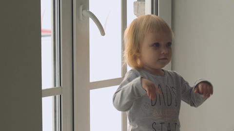 Little baby girl standing near the window and emotionally gesticulates Footage