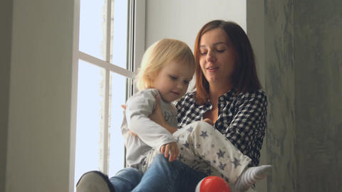 Mother plays with her little baby girl near the window Footage