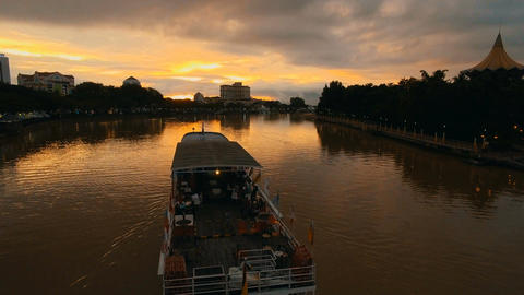 Pleasure boat going through the Sarawak River dyed in sunset Footage