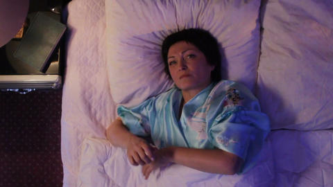 Middle Aged Woman Lies and on Bed under White Warm Blanket Footage