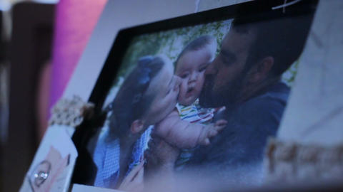 Camera Moves From Happy Family Photo to Baby Girl Photo Footage