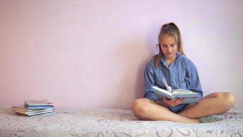 Teen girl doing her homework reading a book Footage