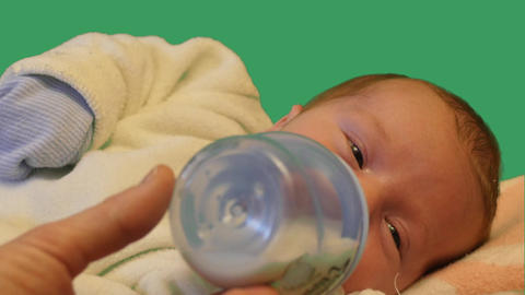 Father feeding newborn baby from a bottle green screen Footage