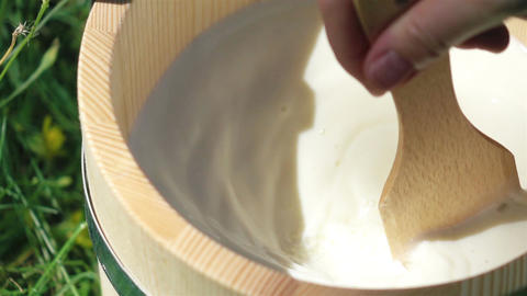 Two videos of milk mixing in wooden bucket in real slow motion Footage