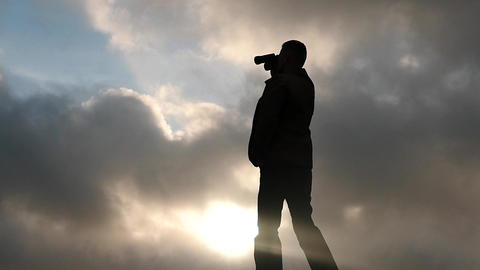 silhouette of man with binoculars clouds background slow motion Footage