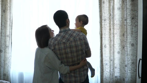 Happy family is standing by the window Footage