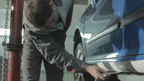 Worker in Uniform Neatly Applies White Putty on Car Bottom Footage