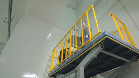 Worker Goes down on Metal Hoist with Yellow Metal Handrails Footage