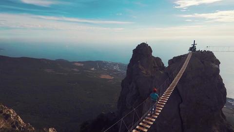 Apic aerial shot of man walking suspension bridge to Cross in Crimea. High rocks Footage