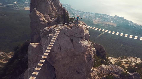 Apic aerial shot of man walking suspension bridge to Cross in Crimea. High rocks