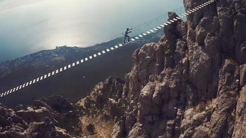 Apic aerial shot of man walking suspension bridge to Cross in Crimea. High rocks Filmmaterial