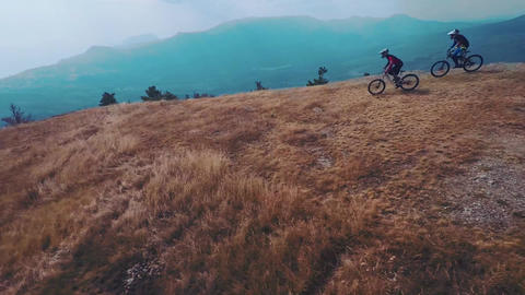 Epic aerial view of mountain bikers ride on mountain in the fog. Cloudy sky, aut ビデオ