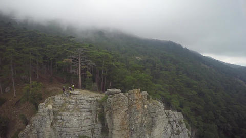 Epic aerial view of mountain bikers standing on mountain in the fog. Cloudy sky Footage