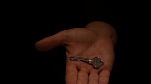 isolated hand with key appears on black background Footage