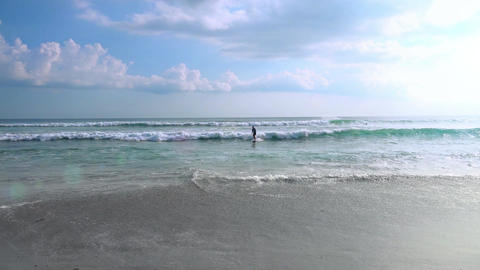 Surfer riding white crested waves and moving out of sea to shore towards camera Footage