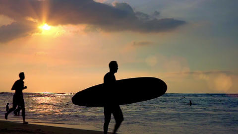 Silhouettes of surfer carrying surfboard and man running along shoreline. Bali Footage