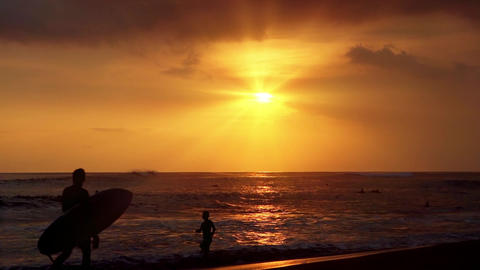Silhouettes of surfers at evening tropical beach. Spectacular sunset Footage