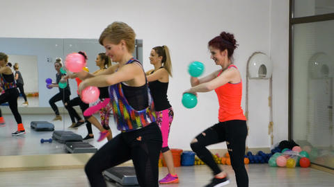 Women working out at the fitness club with stepper and balls in hands Footage
