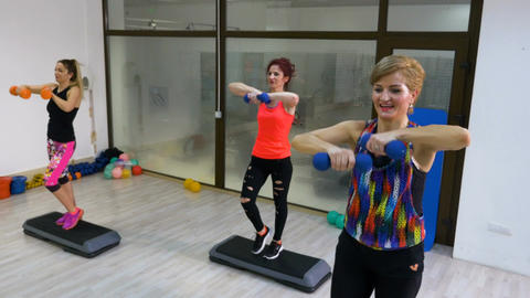 Women doing aerobics sequence with weights in hands Live Action