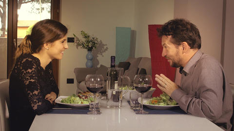 Happy couple toasting with wine during romantic dinner at home Footage