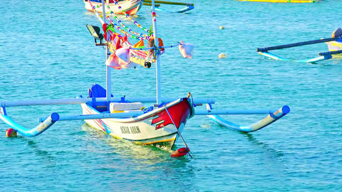 Fishing boats and traditional Balinese outrigger canoes swaying on ocean waves Footage