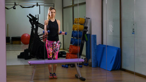 Woman standing in front of mirror making exercise at the fitness gym Footage