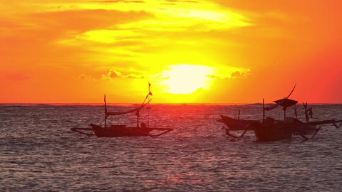 Outrigger fishing boats swaying on sea waves against sunset sky. Bali, Indonesia Footage