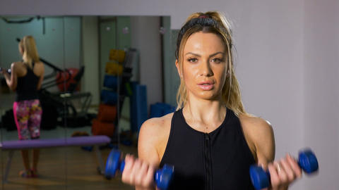 Portrait of strong woman doing body building exercising with dumbbells Footage