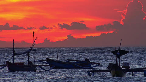 Silhouettes of traditional fishing vessels floating in ocean against red sunset Footage