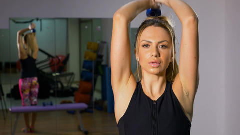 Portrait of fit woman exercising with light weight dumbbells in her hands at the Footage