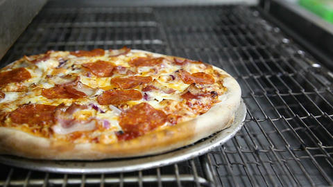 Hissing pizza moves from the oven and the cook takes it on a shovel Footage