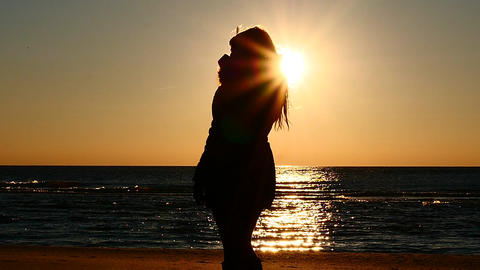 warmly clothed woman drink hot tea before sunset at the seashore slow motion Footage