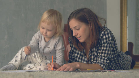 Mother and her little daughter are drawing with pencils in album Footage