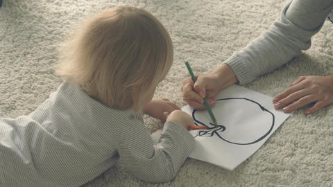 Baby girl with mother paints picture with pencils Footage