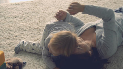 Mother plays with daughter on the floor Footage