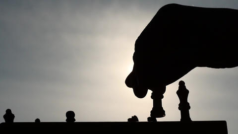 silhouettes of hand and chess figurines in game and thinking process. Hand moves Footage