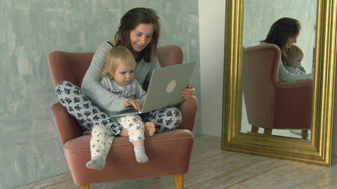 Pretty woman using laptop with little baby on her knees Footage